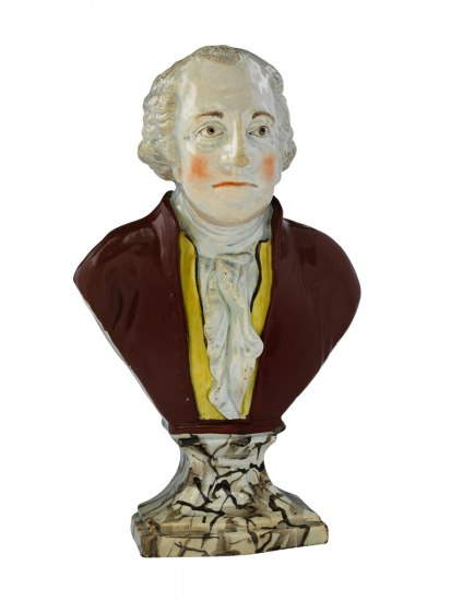 A 1700s bust of George Washington depicts a red-cheeked Washington, unsmiling, clad in a brown jacket with yellow flourishes.