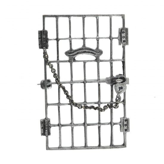 Small metal pin in the shape of a jail cell's door. A chain connects one of the door's hinges to the door's handle. It is secured with heart-shaped lock.