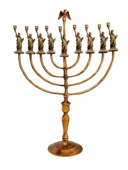 Golden-colored Hanukkah lamp decorated with Statue of Liberty figures and an eagle.
