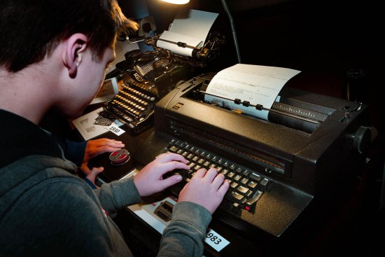 A boy types on a black electric IBM typewriter