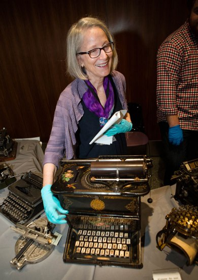 A woman wearing gloves opens a lid on a typewriter to show its all-uppercase keyboard