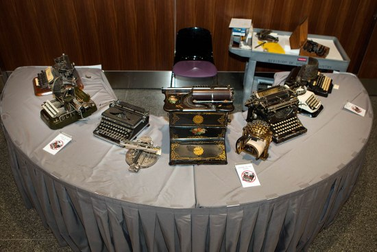 Nine typewriters of varying styles and eras set out on a table