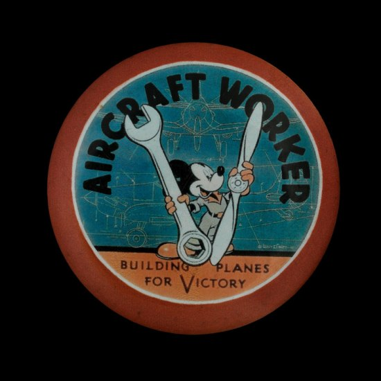 "Button shows Mickey Mouse holding a large wrench and a plane propeller with a blueprint in the background. The text reads: ""Aircraft Worker…Building Planes for Victory"""