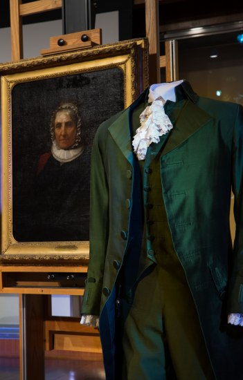 The green suit Lin-Manuel Miranda wore as Hamilton stands in front of a portrait of Eliza Hamilton.
