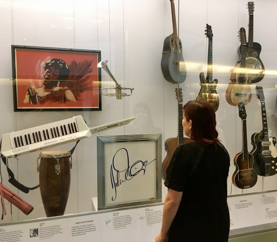 Woman in black dress looking at a museum display featuring drums, painting, and other musical items.