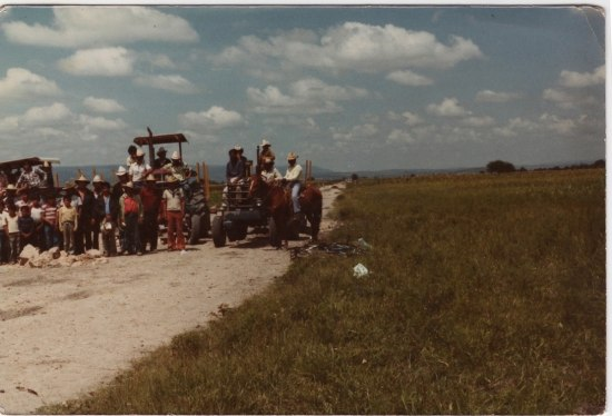 A photograph showing an empty landscape and a group of people on tractors.