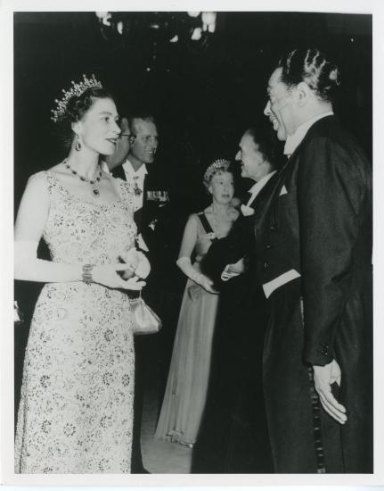 Queen Elizabeth II, in a dress and crown, meets Ellington, in a suit