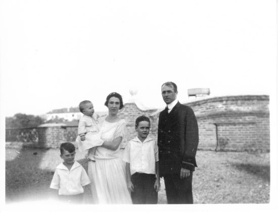 A black and white photograph of a family. A couple and three children of various ages stand in the grass in front of a brick building with a low, sloping roof.