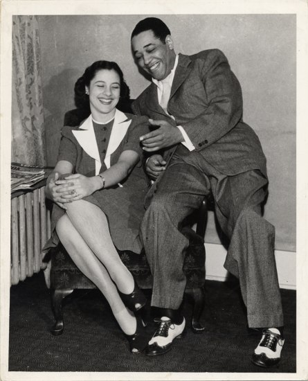Black and white snapshot. A woman sits in a chair, her legs crossed and her hands on knee. She smiles, eyes closed and mouth open to show her teeth. She wears a smart suit with white collar. The man balances on one of the arms of the chair, gesturing toward her, also with a smile. He wears a suit and black/white shoes.