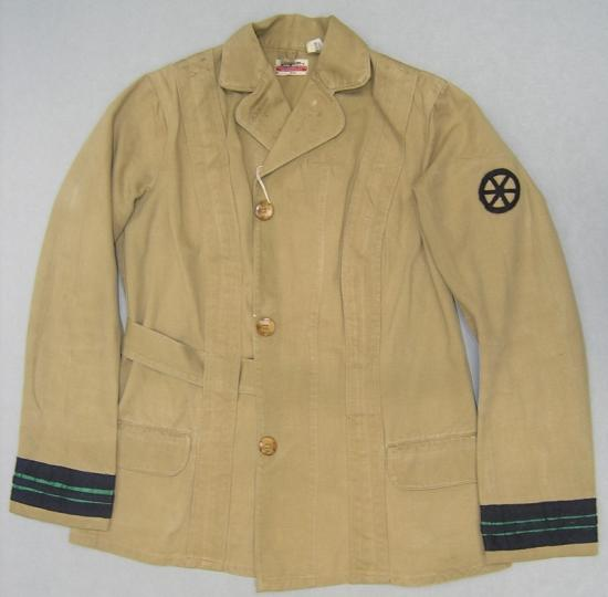 Photo of tan colored jacket with three buttons, navy colored arm bands, and a wheel-shaped insignia on left shoulder.