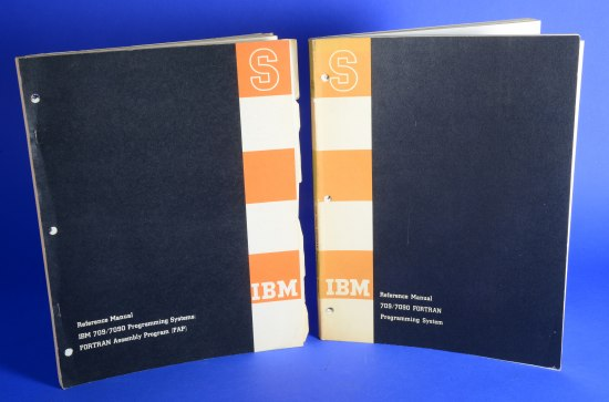 "Two paper manuals standing up for the photo. One is held together with staples. Each has a black cover with a vertical strip in yellow and white. ""IBM"" and ""S"" are on the covers."