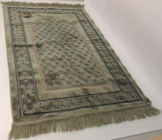 Photo of rug with fringed edges and stone