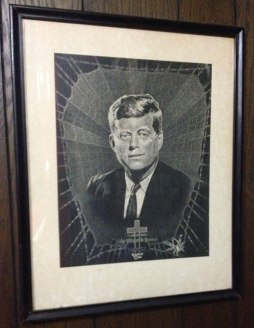 Black and white artwork depicting President Kennedy (head and shoulders) wearing typical suit with calm facial expression. Behind him and around him, he is framed by a spider web design.