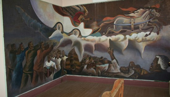 Painted mural that spans two walls and meets in the middle. On left, four African American people lift their arms while a choir dressed in white robes lifts their heads, mouths singing. On right: a chariot with four horses and a rider wearing a red cape flies through the sky. Below the chariot, more African American figures react dramatically, lying on the floor, lowering their heads, appearing to cry. A man with white hair watches, an alarmed look on his face.