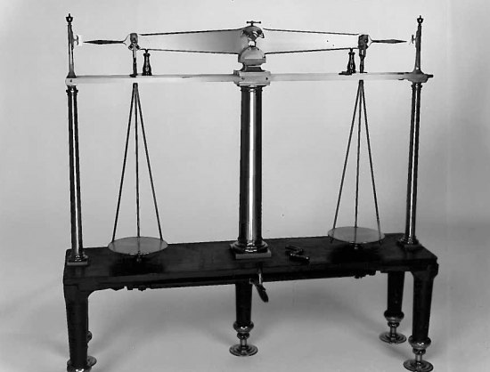Black and white photo of a scale/balance. A central pole has two arms, each has a plate or tray suspended from it.