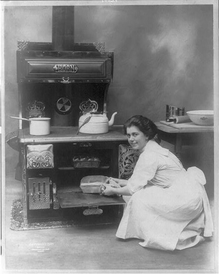 A black and white photo of a woman into a white dress kneeling beside an oven. It has a white kettle and pot resting on the stove. There are baking accoutrements laid out on a table in the background. The woman looks at the camera knowingly as she clasps a loaf of bread in a tin pan with a cloth. The woman's face is the focal point of the photo. Her expression could sell a hundred stoves.