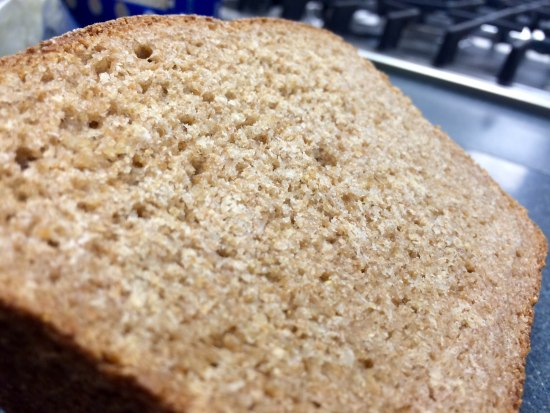 A piece of bread. The picture is taken at an angle so you see across the width of the bread. It is rough in texture.