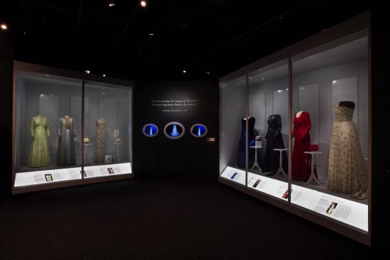 Photo of museum gallery with gowns in display cases.