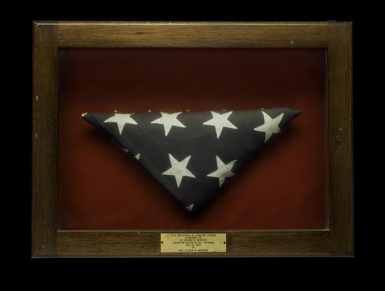 Flag folded triangularly in a wooden case with a gold placard at the bottom