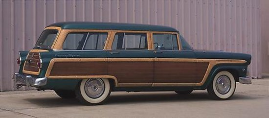 Photograph of a 1955 Ford Station. The car is pine tree green with mahogany-grain-finished imitation-wood panels on the sides.