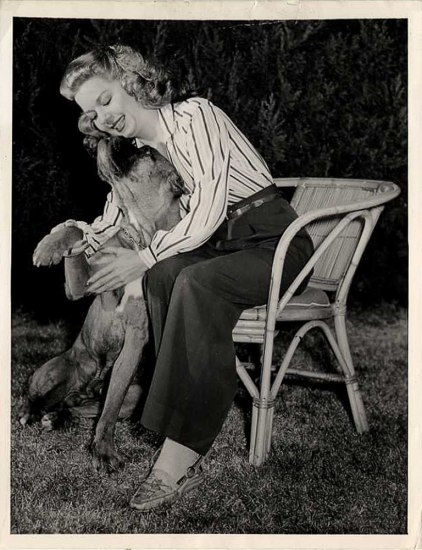 Black and white photo of woman sitting in chair snuggling a dog who raises his head to lick her chin. She is smiling.