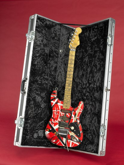 In a black  velvet lined case, a red and white electric guitar.