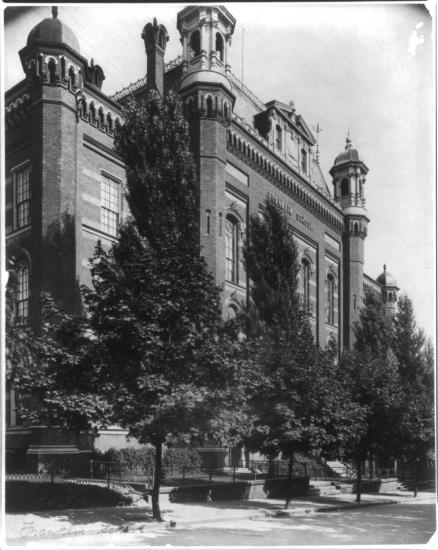 Black and white photo of building with turrets and trees in front