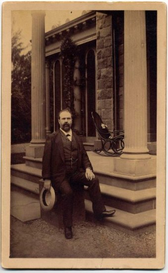 A man in a suit sits in front of a building and columns.