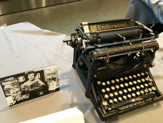 A black and white photo of a woman holding a book (Mildred Wirt Benson) next to an Underwood typewriter out on display at the museum