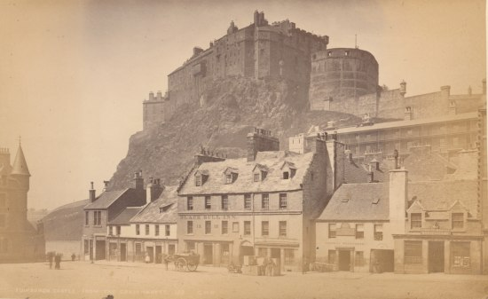 Photograph depicting several buildings of several stories on a street with carriages set against a rocky outcrop with a castle or fort built on top.