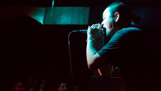 G. Yamazawa holds a microphone and speaks at a performance