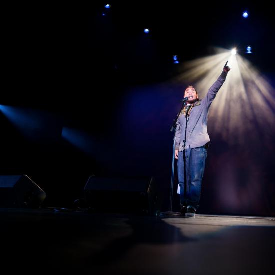 G. on stage pointing up at light