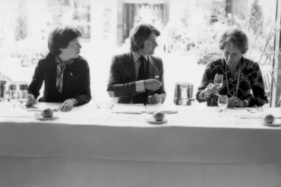 Black and white photo of three people sitting at a table with foliage and courtyard in background. Each has two wine glasses and a piece of bread along with documents and a wine chilling container.