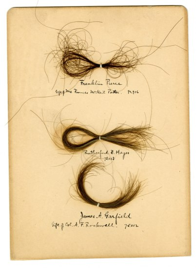 Three locks of hair mounted on to a piece of paper