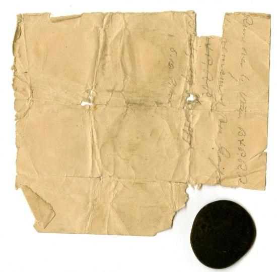 A dark, smashed penny alongside a handwritten note of identification.