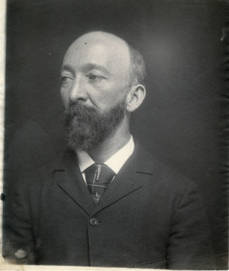 A black and white photograph of a balding, bearded man wearing a suit jacket and tie, looking to his right away from the camera.