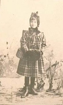 Black and white portrait of a young girl in a plaid coat. Her hair is on top of her head, perhaps in a hat. Her hands are in muff or hand warmer.