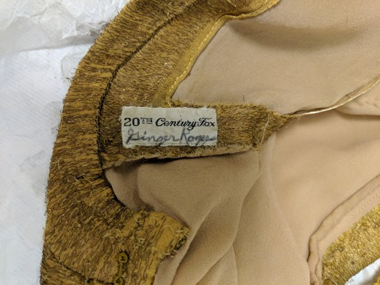 """Photo of a clothing label. In handwritten text, it says """"Ginger Rogers."""" In sewn text, it says """"20th Century Fox."""""""