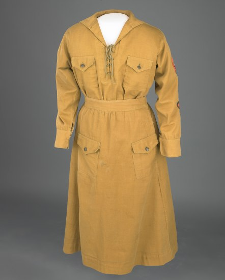 Khaki Girl Scout uniform with four pockets, long sleeves, and lacing at neckline.