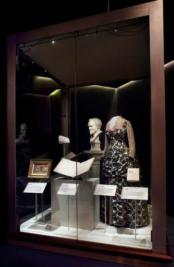 Museum case containing a bust, a gown, paper documents, and a framed painting