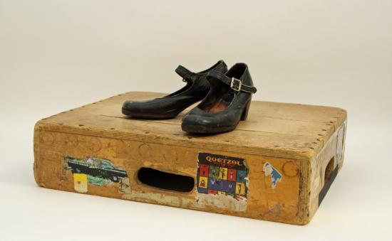 Photograph of brown box with handle and stickers and black shoes