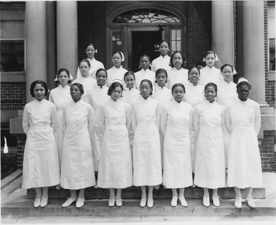 21 women wearing white uniforms (all white cloth, high white collar, white nurse's hat, buttons, white, belt at waist, about mid-calf length, white shoes with low heels and white laces). They pose on the steps of a brick building with columns and door with decorative glass sections. Their facial expressions range from smiles to serious.