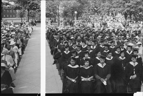 Graduates in caps and gowns, some holding programs or diplomas, sit in chairs. Families sit in nearby chairs as well as in some bleachers. There is an aisle down the left side of the photo. In distance, cars, trees, and a building is visible.