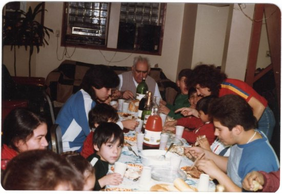 Family gathers around a table full of soda and dishes. An old man sits at the head of the table.