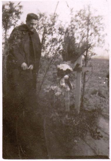 Man stands with bowed head and hat in hand in front of a cross