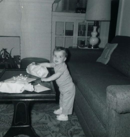 Black and white photo of a small child leaning on coffee table near two presents. Couch, lamp, books, and living room in background. He has on tennis shoes, pants, and shirt.