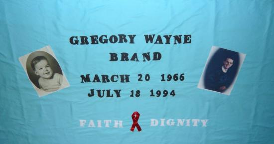 "Turquoise fabric quilt panel with text saying: ""Gregory Wayne Brand, March 20 1966 - July 18 1994, Faith and Dignity."" There are two portraits of Greg, one as a smiling baby and one as a young man. There is a red ribbon between ""Faith"" and ""Dignity."""