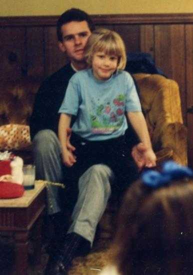Little girl, smiling, sits on the lap of her uncle. They hold hands.