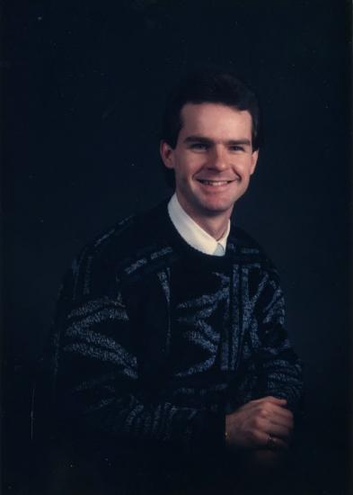 Studio portrait of man, sitting, smiling, wearing sweater, against black background