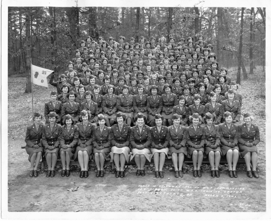 A black and white photograph, in which rows of women in uniforms sit outside surrounded by trees, looking at the camera, many smiling